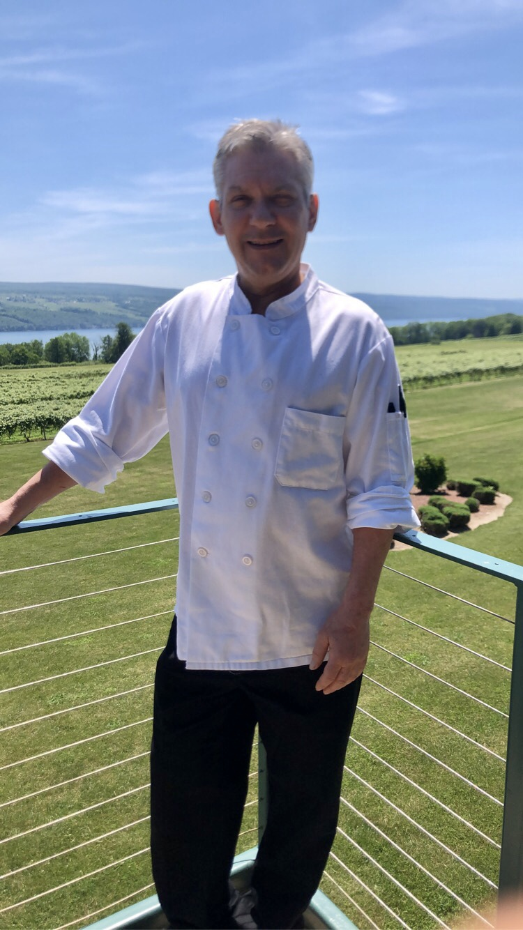 Image of Executive Chef Charlie Metzger, wearing a white chef coat and black pants, standing on a staircase in front of a large lawn and vineyard.